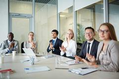 Happy managers clapping hands at conference Stock Photos