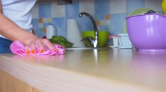 Woman hand is cleaning kitchen worktop with a rag and throwing it at the table Stock Footage