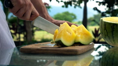 Male hands cutting melon on table in the garden, super slow motion Stock Footage