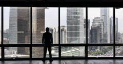 4k,businessman back raising victory arm & Overlooking the building from window. Stock Footage