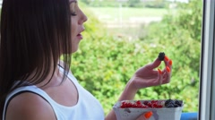 Young woman looking out the window and eating fruits. Park background Stock Footage