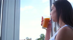 Young woman looking out the window and drinking carrot juice. City background Stock Footage