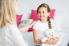 Happy girl with pigtail smiling at her mother Stock Photos