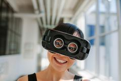 Cheerful young woman wearing virtual reality goggle Stock Photos