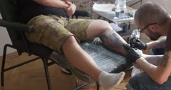 Tattoo artist working, man enjoying tattooing Stock Footage