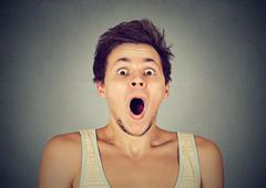 Shocked surprised young man in full disbelief screaming Stock Photos