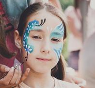 Female child face painting, making butterfly process Stock Photos