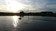 Aerial view of wakeboarding at sunset Stock Footage