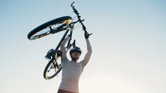 A bicycle rider picks up a bicycle on a background of blue sky. Slow motion Stock Footage