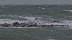 Slow motion - stormy seas breaking on rocky spit of land in clouds Stock Footage