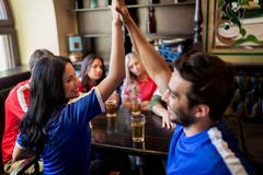 Football fans with beer celebrating victory at bar Stock Photos