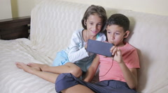 Teenagers using smartphone with earphones. brother and sister with a phone Stock Footage