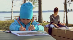 Child is drawing in the album in the Park with his mom. Little girl painting Stock Footage