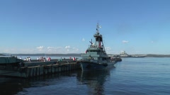 "At the pier fire boat, cruiser ""Admiral   Kuznetsov"" in the distance. Stock Footage"