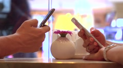 Girl and man continuously tapping their mobile phone touchscreens in a cafe Stock Footage