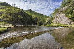 Dovedale reflections, hikers on stepping stones and Thorpe Cloud, limestone Stock Photos