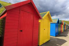Row of colourful beach huts and their shadows, with grassy cliffs, West Cliff Stock Photos