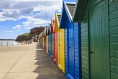 Row of colourful beach huts and their shadows, distant surfers in sea, West Stock Photos