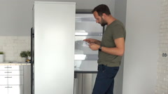 Young man with instruction checking new fridge at his new home Stock Footage