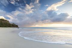 The sky turns pink at sunset and reflected on Ffryes Beach, Antigua, Antigua and Stock Photos