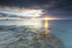 The lights of sunset are reflected in the blue sea, Hawksbill Bay, Antigua, Stock Photos