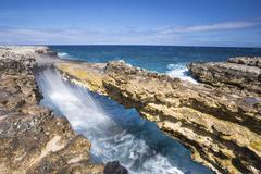 Waves in the natural arches of limestone Devil's Bridge, Antigua, Antigua and Stock Photos