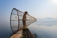 A basket fisherman on Inle Lake prepares to plunge his cone shaped net, Shan Stock Photos