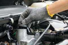 A mechanic is opening the oil cap from a car engine. Stock Photos