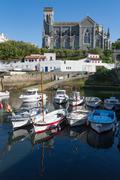 Small port with traditional fishing boats and Eglise Sainte Eugenie in Biarritz, Stock Photos