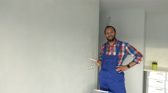 Portrait of happy male worker painting wall at new home  Stock Footage