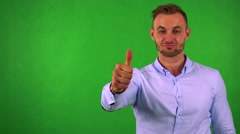 Young handsome business man shows thumb up on agreement - green screen - studio Stock Footage