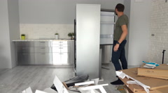 Portrait of happy man unpacking and checking new fridge at home Stock Footage
