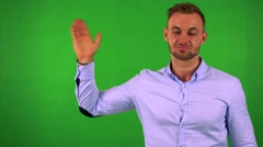 Young handsome business man waves with hand - green screen - studio Stock Footage