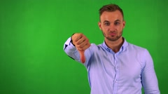 Young handsome business man disagrees (show thumb down) - green screen - studio Stock Footage