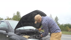 Man checking car engine oil, vehicle safety. The driver on the road at the ro Stock Footage