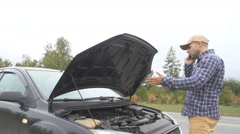 Men opens the car hood and visually inspects examines the motor engine. The c Stock Footage