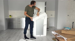 Young man unpacking new fridge from box at home Stock Footage