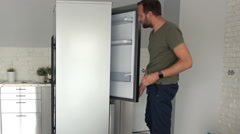 Young man unpacking new fridge at home Stock Footage