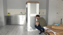 Young man unpacking new fridge from box at home, timelapse Stock Footage