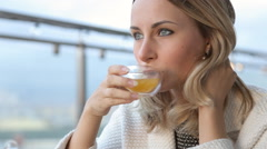 Beautiful happy young woman drinks tea at the cafe in the morning. Stock Footage