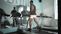 Man running on treadmill in fitness gym Stock Footage