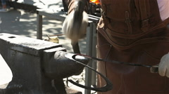 The blacksmith banging a hammer on a metal workpiece Stock Footage