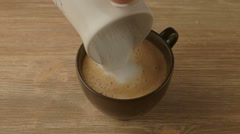 Coffee maker pouring hot milk in cup to prepare cappuccino Stock Footage