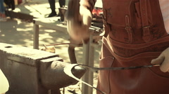 The blacksmith banging a hammer on an anvil with a metal workpiece Stock Footage