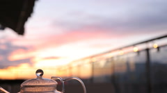 Kettle with tea on the table in a cafe sunset Stock Footage