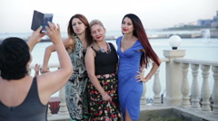 Girls in evening dresses posing on the foregroung of waterfront Stock Footage