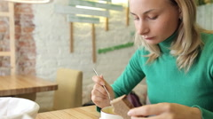Happy, beautiful woman eating tasty soup in cafe in the city Stock Footage