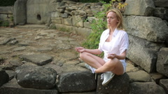 Woman sitting and meditating on stone dolmen Stock Footage