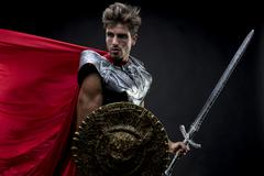 Gladiator, centurion or Roman warrior with iron armor, military helmet with h Stock Photos