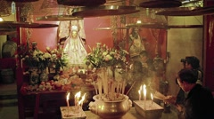 Buddhist worshippers pray inside Man Mo Temple Stock Footage